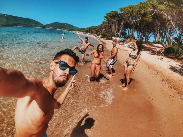 družba mladih na plaži v modnih kopalkah